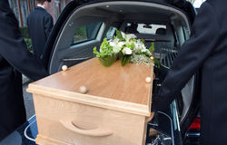 Mourning car. Bearers are carrying a coffin in a mourning car Royalty Free Stock Photos