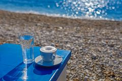 Mourning coffee on the beach. Coffee on the table on the sanny beach royalty free stock photos