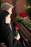 Mourning Couple at Funeral with coffin. Morning man and woman on funeral with red rose standing at casket or coffin Royalty Free Stock Photography