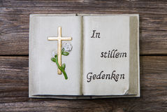 Mourning: cross and german text on a book of stone. Stock Image