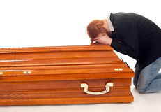 Mourning - crying woman kneeling near coffin Royalty Free Stock Photography