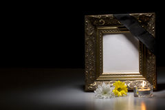 Mourning frame with flowers and candle. Golden mourning frame with flowers and candle on dark background Stock Images