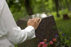 Mourning at grave 1. Female mourns at a grave marker stock images