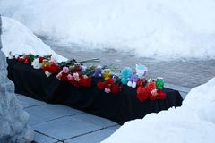 A mourning memorial with flowers and toys after disaster with the victims. Winter, snow. A mourning memorial with flowers and toys after disaster with the Stock Image