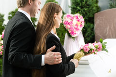 Mourning People at Funeral with coffin. Mourning men and women on funeral with pink rose standing at casket or coffin Royalty Free Stock Images