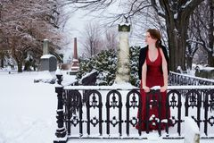 Mourning Teen. Beautiful teen girl grieving in a snow covered cemetary Stock Photography