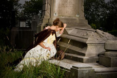 Mourning on a tomb. Young woman in victorian dress mourning on a tomb Stock Image