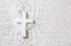 Mourning: white ceramic cross on grey ornament background. Stock Photos