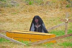 Mourning Widow next to coffin Stock Image