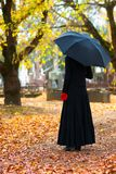 Mourning Woman. Woman in Mourning at Cemetery in Fall, with Black Umbrella Royalty Free Stock Image
