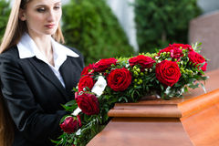 Mourning Woman at Funeral with coffin. Mourning woman on funeral with red rose standing at casket or coffin stock image
