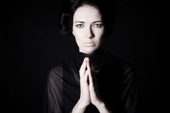 Mourning. Young beautiful girl praying. on a black background Royalty Free Stock Images