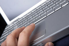 Mouse Click. A hand clicking on a one button mouse on a laptop computer - focus on finger Royalty Free Stock Photos
