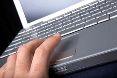 Mouse Click. A hand clicking on a one button mouse on a laptop computer - focus on finger Stock Photos