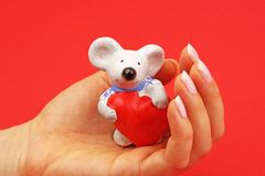 Mouse figurine. Holding heart placed in a female open hand with red background Royalty Free Stock Photo