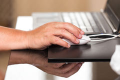 Mouse in hand at work on laptop Royalty Free Stock Images