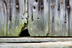 Mouse Hole in Old Wood Barn Wall. Mouse entrance and exit hole at the bottom of an antique barn wood wall on an old house royalty free stock image