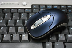 Mouse On Keyboard. A wireless mouse put on keyboard of a laptop stock image