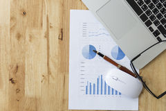 Mouse, laptop computer and market analysis business chart Royalty Free Stock Photos