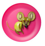 Mouse made of kiwi and apple. On pink plate royalty free stock photography
