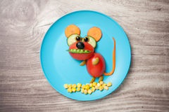 Mouse made of vegetables on plate and table Stock Photography