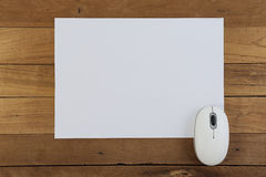 Mouse and paper on wood table Royalty Free Stock Photos