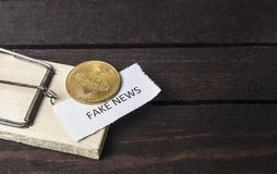 Mouse trap, bitcoin and the word: fake news. Royalty Free Stock Images