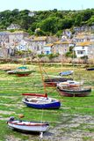 Mousehole In Cornwall. The Cornish fishing village of Mousehole with beached fishing boats in the harbour and cottages in the background Stock Photo