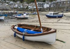 Harbor Mousehole Sail Boat. Mousehole, England - April 28, 2017: Harbor of Mousehole with fishing boats, sail boat, houses and low tide, Cornwall Royalty Free Stock Photo
