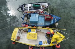Three Fishing Boats in Mousehole. Mousehole, England - April 28, 2017: Three fishing boats with nets, yellow boxes and ropes in Cornwall Stock Photos