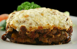Moussaka. Lamb moussaka with egg plant cheese and salad royalty free stock photos
