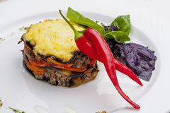 Moussaka of lamb on a white plate. Lobio from green beans on a white plate on white background stock photos