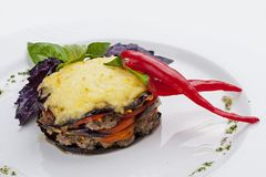 Moussaka of lamb on a white plate. Lobio from green beans on a white plate on white background stock images