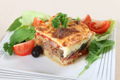 Moussaka and salad. A traditional Greek moussaka, made with layers of potato, aubergine, meat, and tomato sauce, topped with bechamel sauce and served with salad stock images
