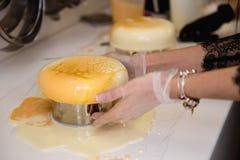 Mousse κέικ γιαουρτιού Τα κορίτσια μαγειρεύουν και δημιουργούν ένα σχέδιο mousse στο κέικ Παγωμένη τήξη καθρεφτών στο κέικ μαγειρ στοκ εικόνα