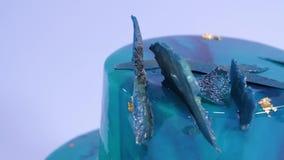 Mousse κέικ που διακοσμείται στο θαλάσσιο ύφος που καλύπτεται με το μπλε λούστρο καθρεφτών και τα άσπρα θαλασσινά κοχύλια σοκολάτ φιλμ μικρού μήκους