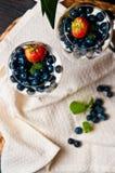 Mousse μάγκο με τα βακκίνια στα γυαλιά κρασιού στοκ εικόνες