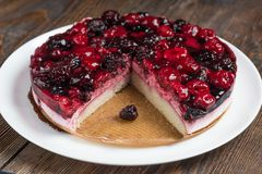 Mousse cake with berries on wooden background royalty free stock image