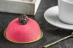 Mousse cake with marzipan and vintage spoon for breakfast. Coffee with mousse cake for dessert with blackberries on a dark background Stock Image