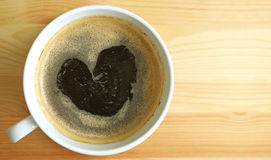 Mousse chaude de café noir de forme de coeur, vue supérieure avec l'espace libre sur la table en bois pour la conception Images stock