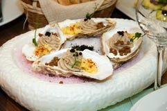 Mousse da un'ostrica con l'ananas e le fette di pane in un lavandino su un vassoio con ghiaccio Fotografie Stock Libere da Diritti