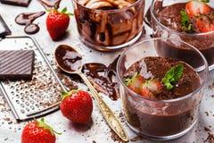 Mousse de chocolate con las fresas en vidrio en la tabla rústica Foto de archivo libre de regalías