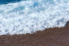 Mousse de mer Les coupures de vague au sujet du rivage Image stock