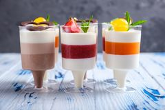 Mousse desserts in wineglasses, decorated chocolate, strawberry, mint and cocktail cherries on aged wooden table. Layered mousse desserts in wineglasses stock image