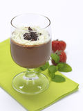 Mousse in a glass. A chocolate flavor dessert served in a glass and decorated with strawberries and menthe stock images