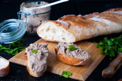 Mousse, pate in a jar with baguette and parsley. Mousse, pate in a jar with a baguette and parsley on a wooden background dark Stock Images