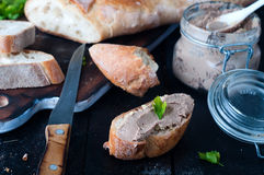 Mousse, pate in a jar with baguette and parsley. Mousse, pate in a jar with a baguette and parsley on a wooden background dark Stock Photo