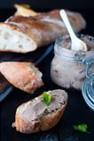 Mousse, pate in a jar with baguette and parsley. Mousse, pate in a jar with a baguette and parsley on a wooden background dark Royalty Free Stock Images
