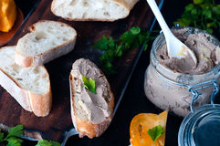 Mousse, pate in a jar with baguette and parsley. Mousse, pate in a jar with a baguette and parsley on a wooden background dark Royalty Free Stock Photos