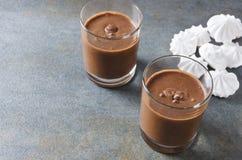 Mousse savoureuse avec du chocolat Deux tasses en verre complètement de souris de chocolat sur la table rustique grise L'espace v photographie stock
